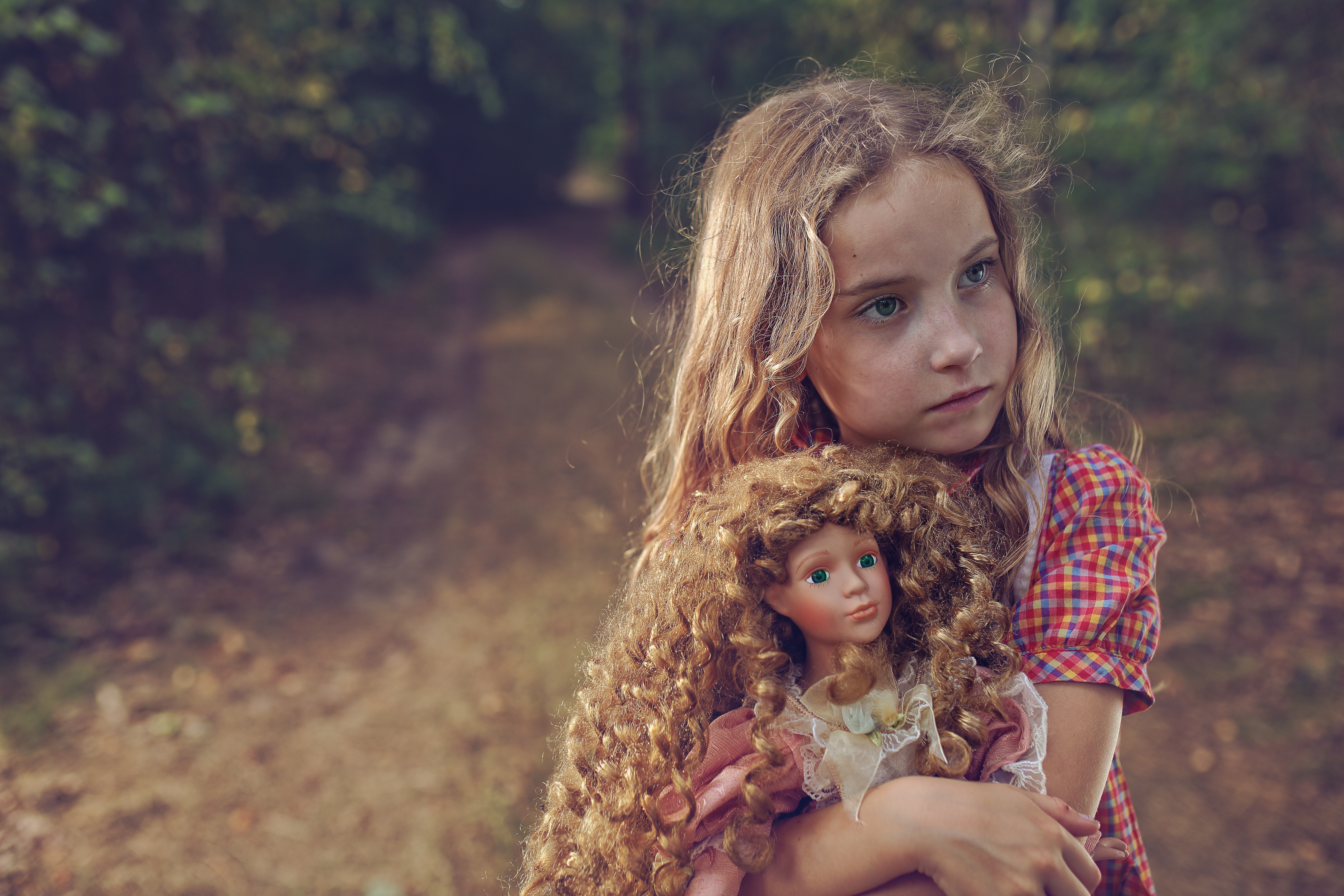 Pensive and mysterious young girl with a doll